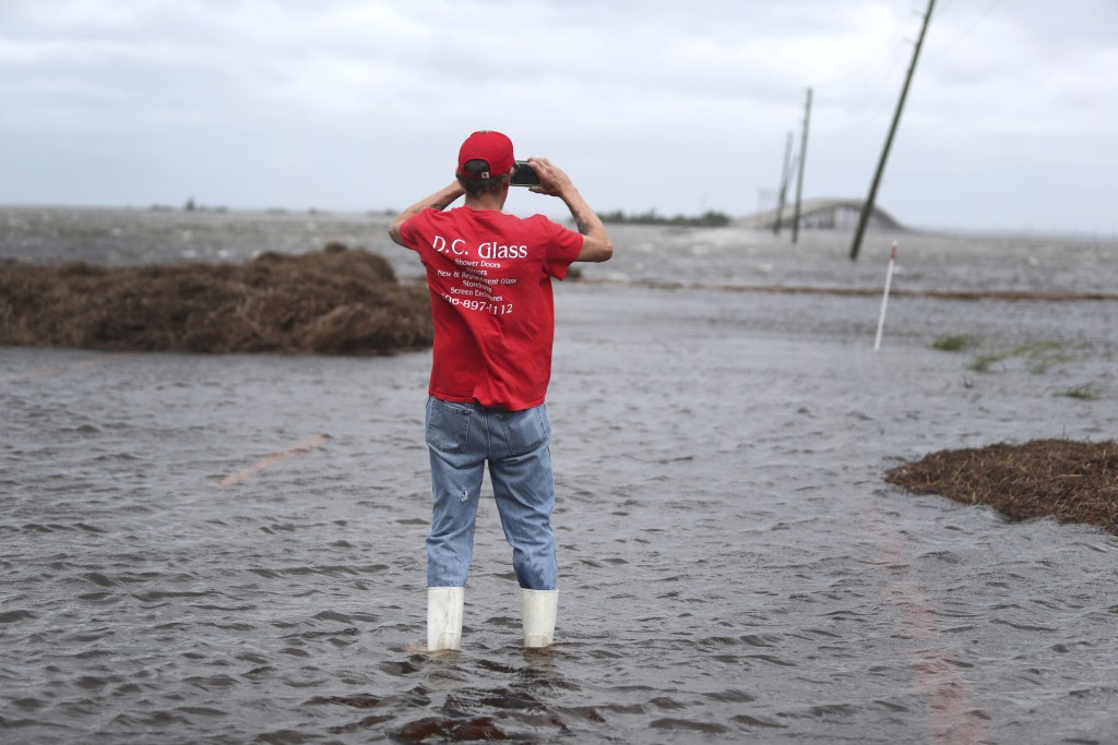Mike Rogers takes a photo of the storm surge from Hurricane Dorian that blocks Cedar Island off from the mainland on NC 12 in Atlantic, N.C., after Hu...