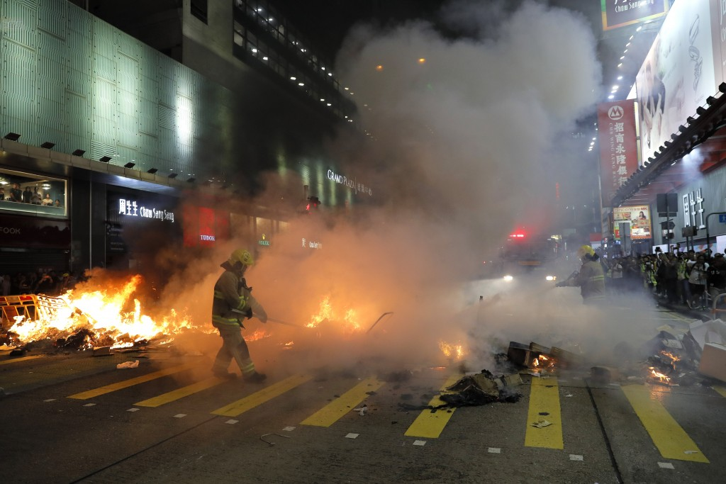 Firefighters put out fire by protesters during a protest in Mong Kok, in Hong Kong on Friday, Sept. 6, 2019. The ratings agency Fitch on Friday cut Ho