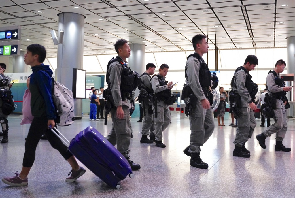 Riot police patrol at airport express central station in downtown Hong Kong, Saturday, Sept. 7, 2019. Hong Kong authorities were limiting airport tran