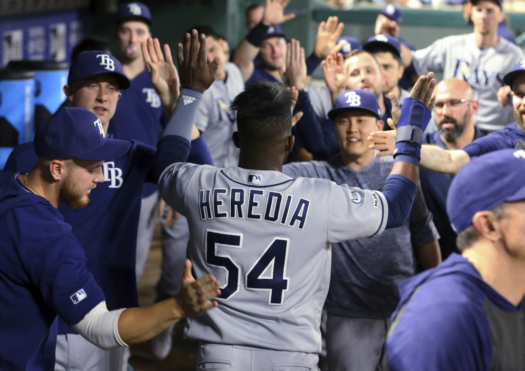 Tampa Bay Rays' Guillermo Heredia (54) is greeted in the dugout after scoring on a single by Joey Wendle during the fifth inning of the team's basebal...