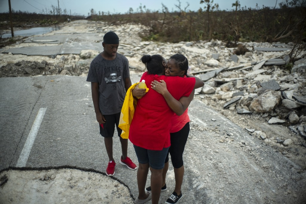 Brennamae Cooper, right, cries and hugs a friend after finding themselves walking in opposite directions, one escaping the destruction of Hurricane Do...