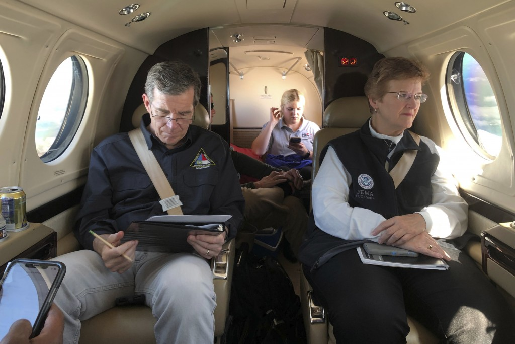 North Carolina Gov. Roy Cooper, left, makes notes on a report as FEMA Coordinating Officer Libby Turner looks out the window of their plane on the way...
