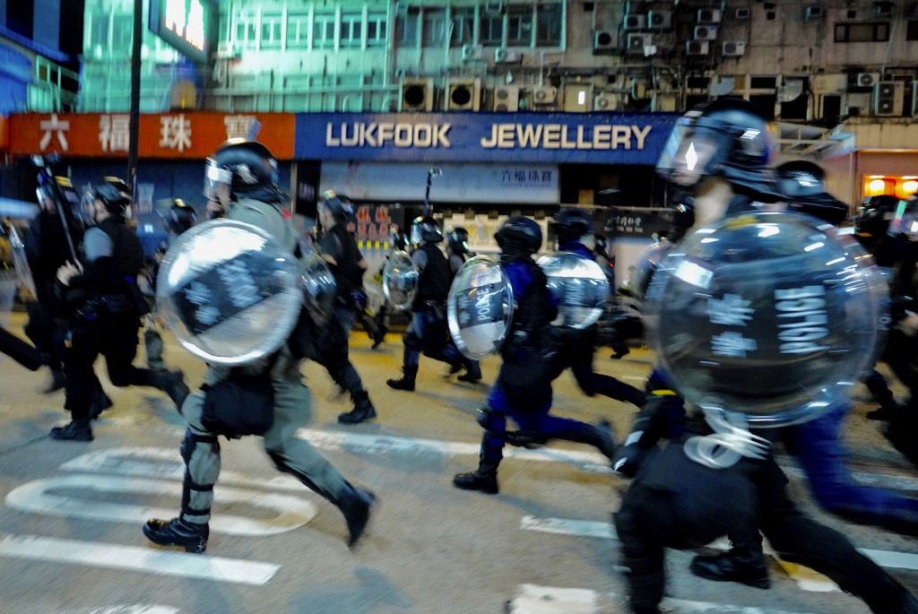 Protestors face police chase protesters during a protest in Nathan road, Hong Kong on Friday, Sept. 6, 2019. The ratings agency Fitch on Friday cut Ho