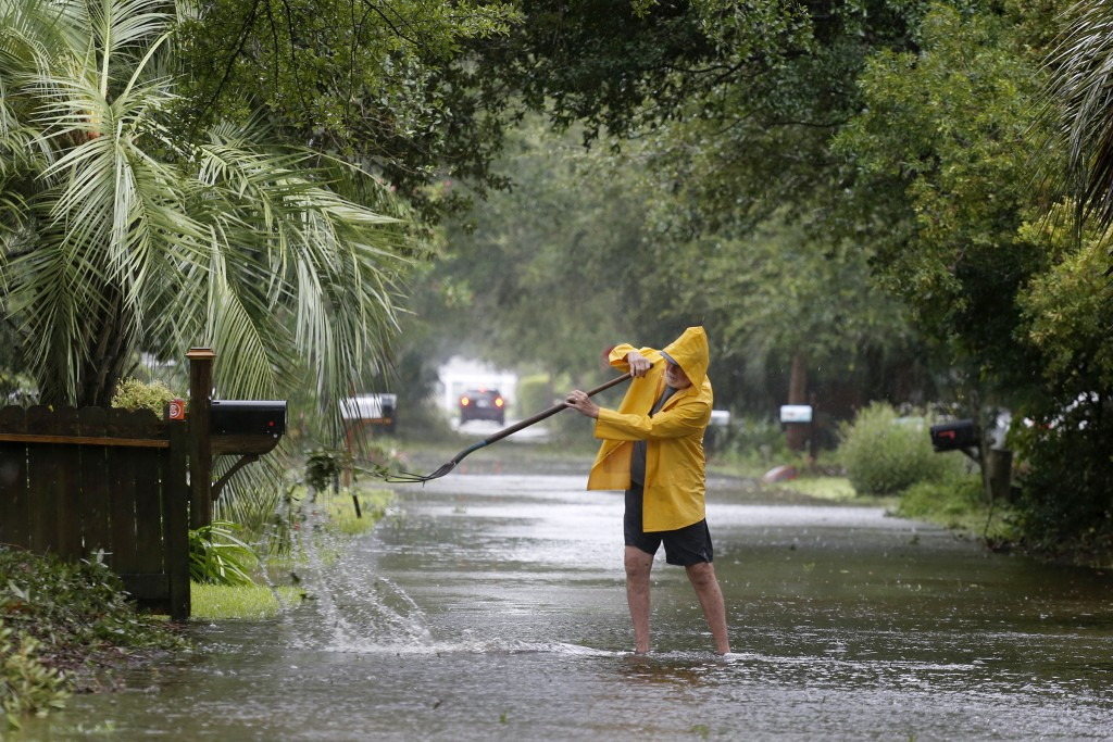 An Isle of Palms resident clears the drain on Hartnett Blvd. during Hurricane Dorian at the Isle of Palms, S.C., Thursday, Sept. 5, 2019, in Charlesto...