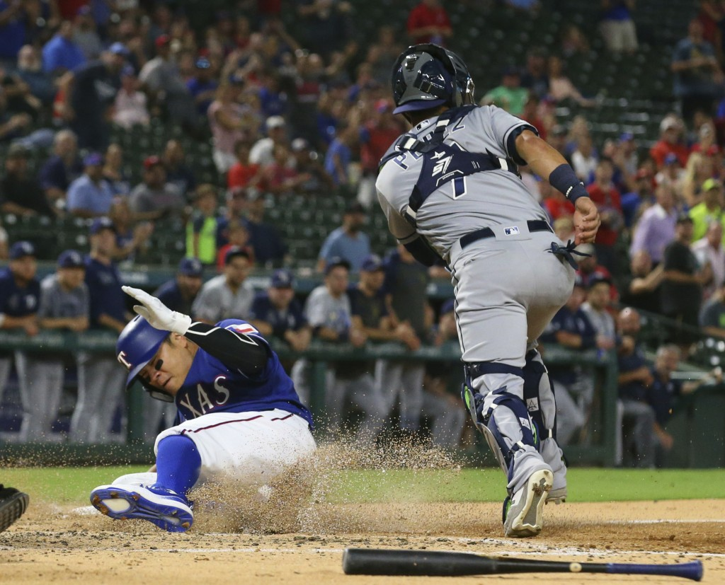 Texas Rangers Shin-Soo Choo slides home to score on a double by Willie Calhoun ahead of the throw to Tampa Bay Rays catcher Michael Perez during the f...