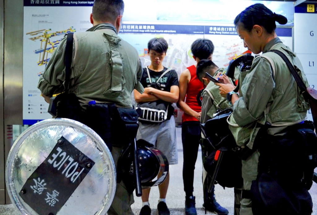 Riot police check passengers' bags at airport express central station in downtown Hong Kong, Saturday, Sept. 7, 2019. Hong Kong authorities were limit