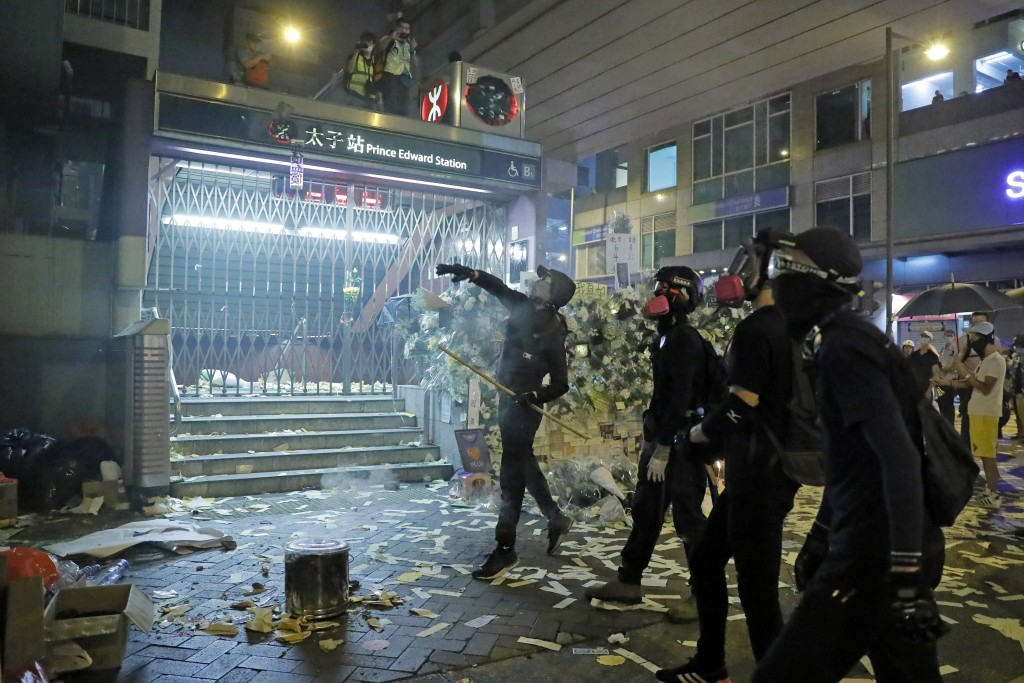 Protesters throw brick to a police station in Hong Kong on Friday, Sept. 6, 2019. The ratings agency Fitch on Friday cut Hong Kong's credit rating and