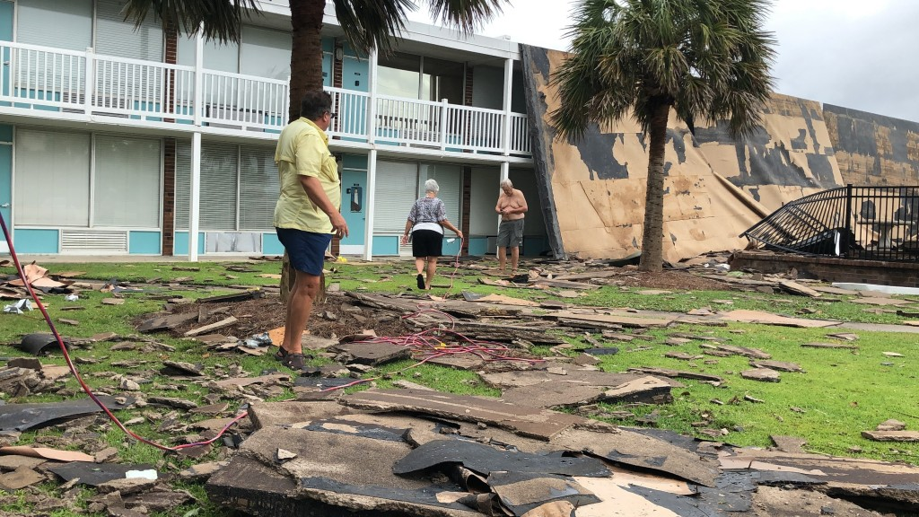 Residents of the Bogue Shores condominiums work to hook up a generator after the complex lost its roof during high winds from Hurricane Dorian in Atla...
