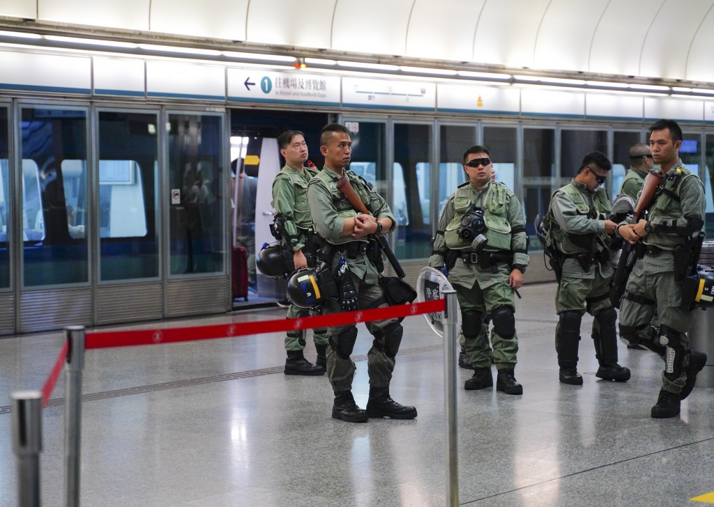 Riot police stand guard at airport express central station in downtown Hong Kong, Saturday, Sept. 7, 2019. Hong Kong authorities were limiting airport