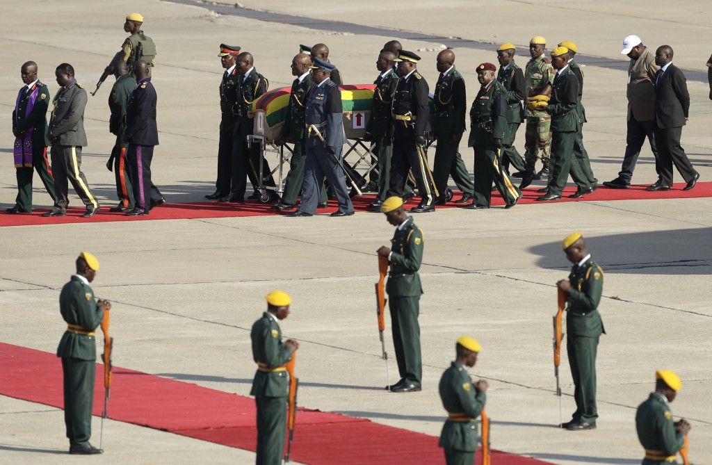 A coffin carrying the remains of Zimbabwe's longtime ruler Robert Mugabe arrives from Singapore, at the RG Mugabe International Airport in Harare, Wed