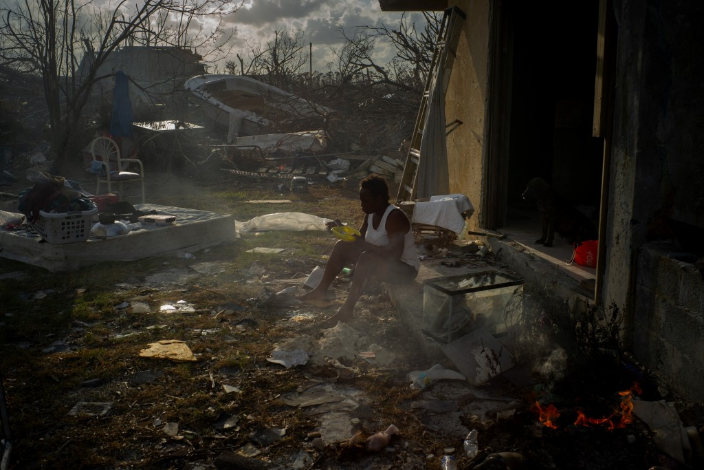 Tereha Davis, 45, eats a meal of rice as she sits among the remains of her shattered home, in the aftermath of Hurricane Dorian in McLean's Town, Gran...