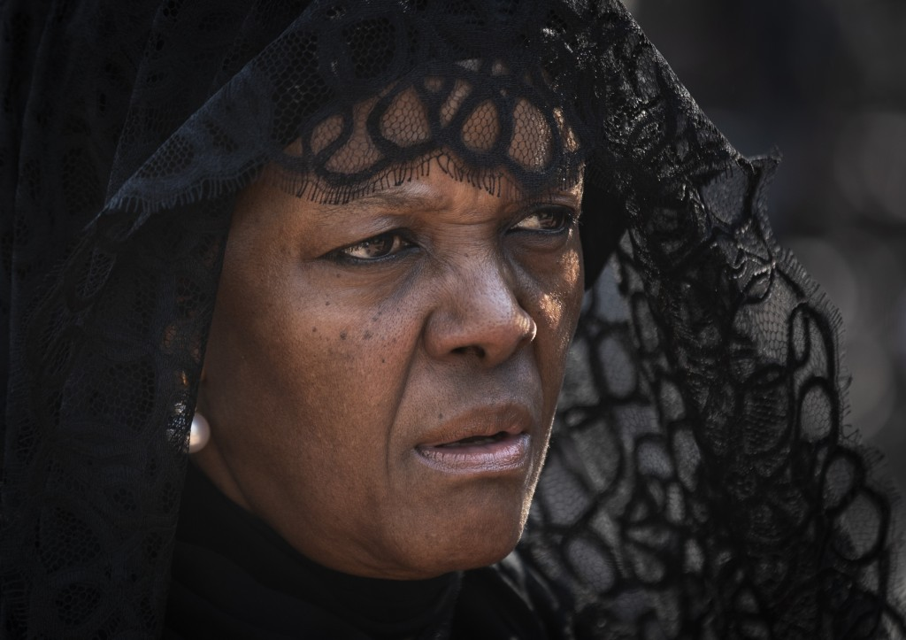 Widow Grace Mugabe wears a black veil as she follows the casket of former president Robert Mugabe to an air force helicopter for transport to a stadiu