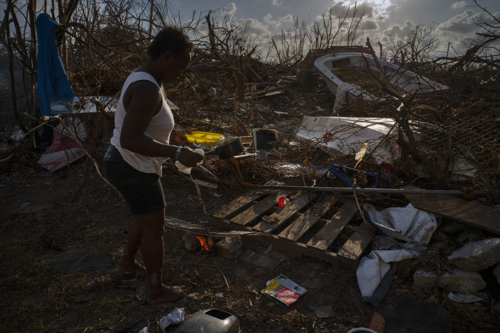 Tereha Davis, 45, holds a plate of rice as she walks among the remains of her shattered belongings, in the aftermath of Hurricane Dorian, in McLean's ...
