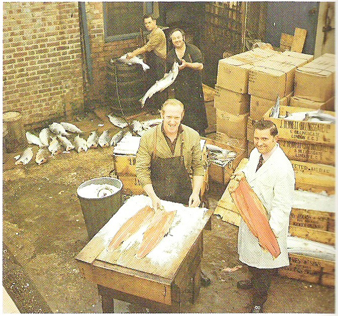 In this 1960 photo provided by H. Forman & Son, Marcel Forman, right, Lance Forman's father in the salmon curing yard in London. Forman's family has b...