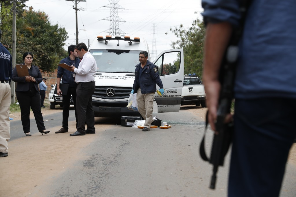 Police inspect the area near the bullet ridden vehicles left after a shootout when jailed drug lord Jorge Teofilo Samudio Gonzalez escaped from custod