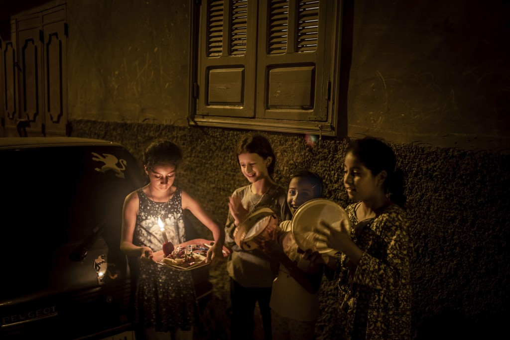 In this Monday, Sept. 9, 2019 photo, girls carry a tray and play with drums outside their home to collect treats and dry fruits, in celebration of Ash...