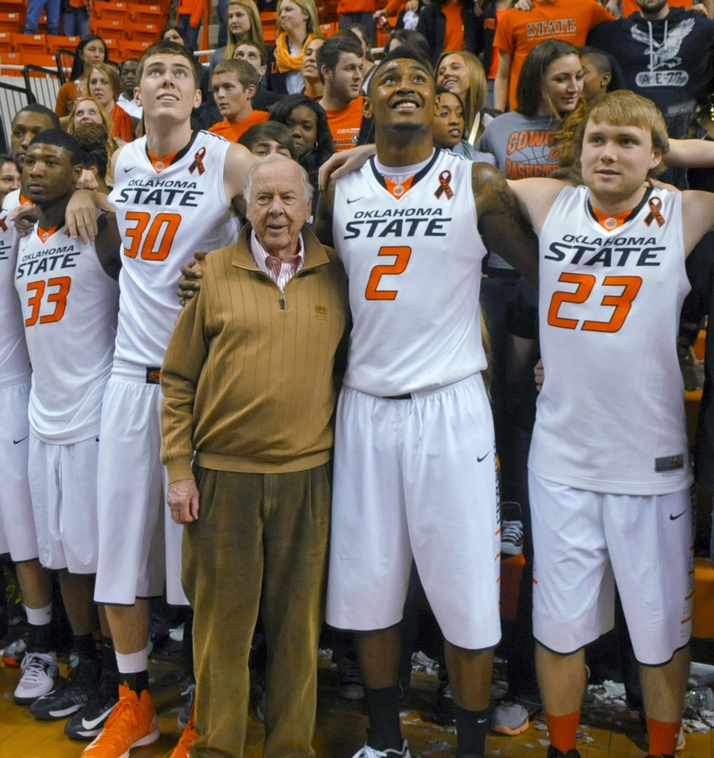 FILE - In this March 2, 2013, file photo, oil tycoon and Oklahoma State supporter T. Boone Pickens, center, celebrates with Oklahoma State's basketbal...