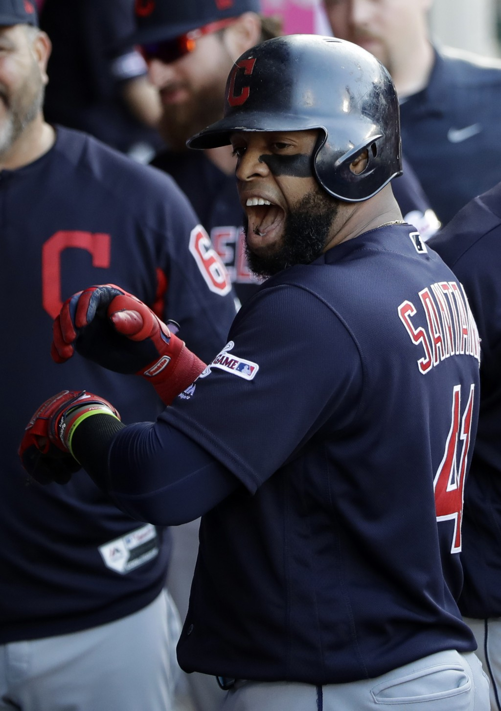 Cleveland Indians' Carlos Santana celebrates in the dugout after his solo home run against the Los Angeles Angels during the first inning of a basebal...