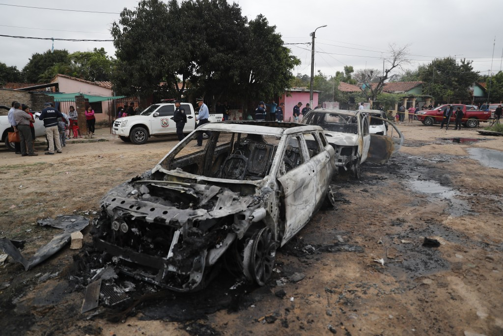 Police guard three torched vehicles after jailed drug lord Jorge Teofilo Samudio Gonzalez escaped from custody, in Asuncion, Paraguay, Wednesday, Sept...