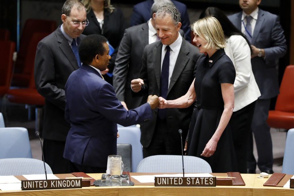 New U.S. Ambassador Kelly Craft receives a fist bump greeting from South Africa's Ambassador Jerry Matjila, left, as she attends her first Security Co...
