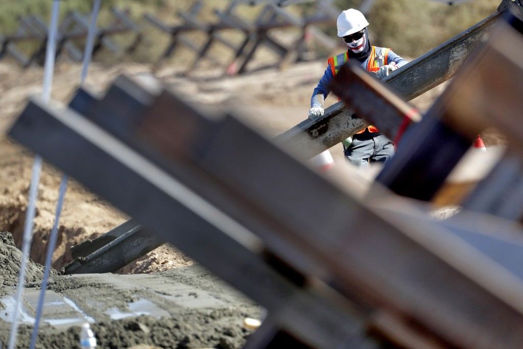 A government contractor, surrounded by existing Normandy barriers that separate Mexico and the United States, pours a concrete footer in preparation f