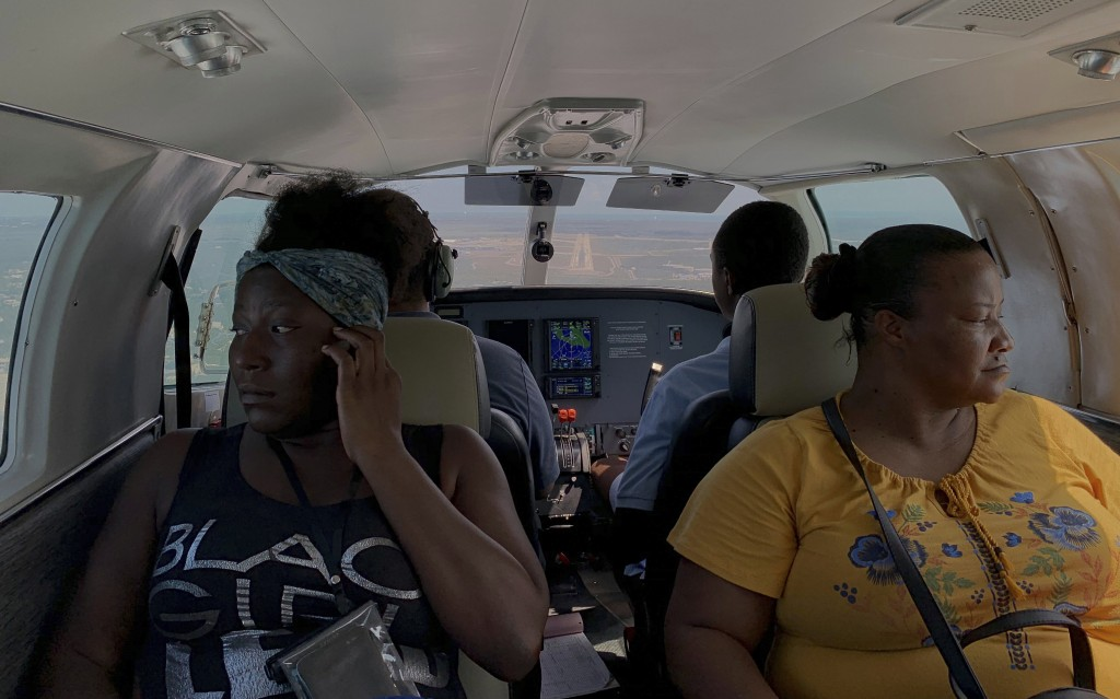 Dimple Lightbourne, left, and her mother Carla Ferguson sit in a plane as it approaches to land in Nassau after they were evacuated from Abaco Island,...