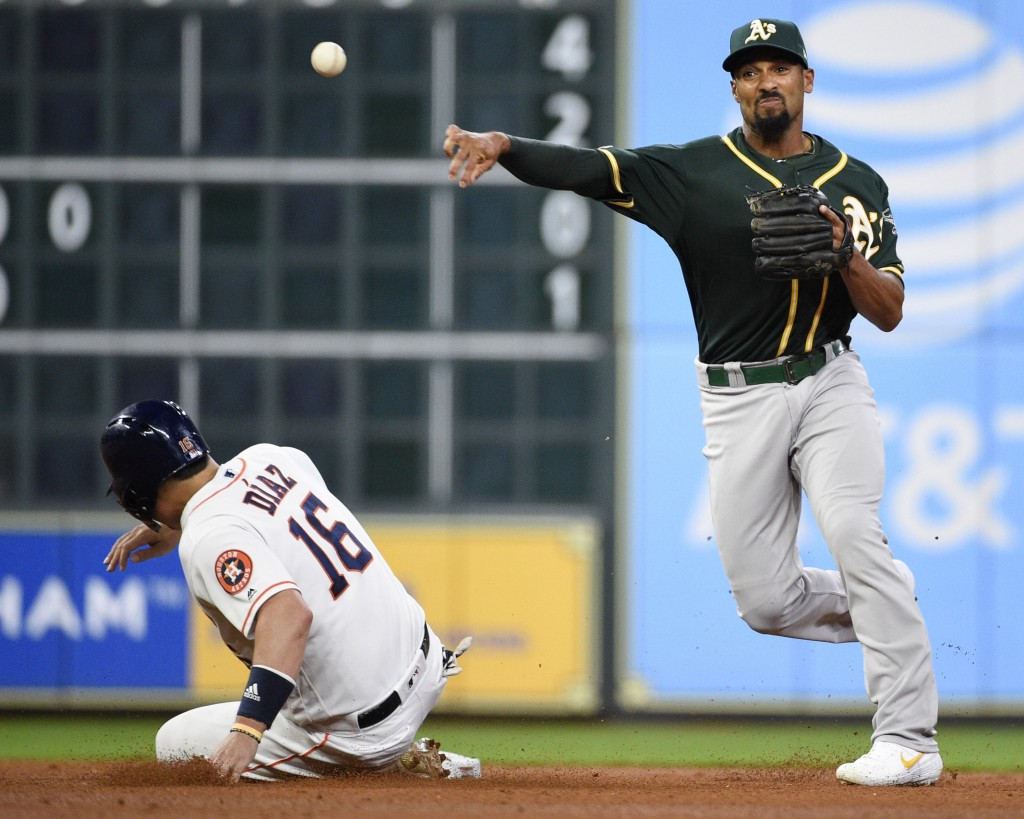 Oakland Athletics shortstop Marcus Semien, right, attempts a double play over Houston Astros' Aledmys Diaz during the second inning of a baseball game...