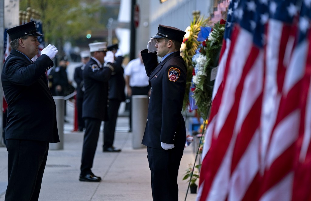 New York City firefighters salute in front of a memorial on the side of a firehouse adjacent to One World Trade Center and the 9/11 Memorial site duri...