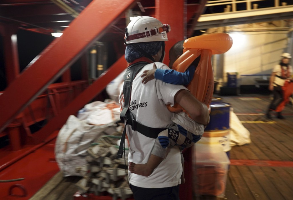 A toddler who was rescued at sea by a 14-meter sailboat Josefa, run by the group Resqship, is carried by a medic after being transferred onto the huma