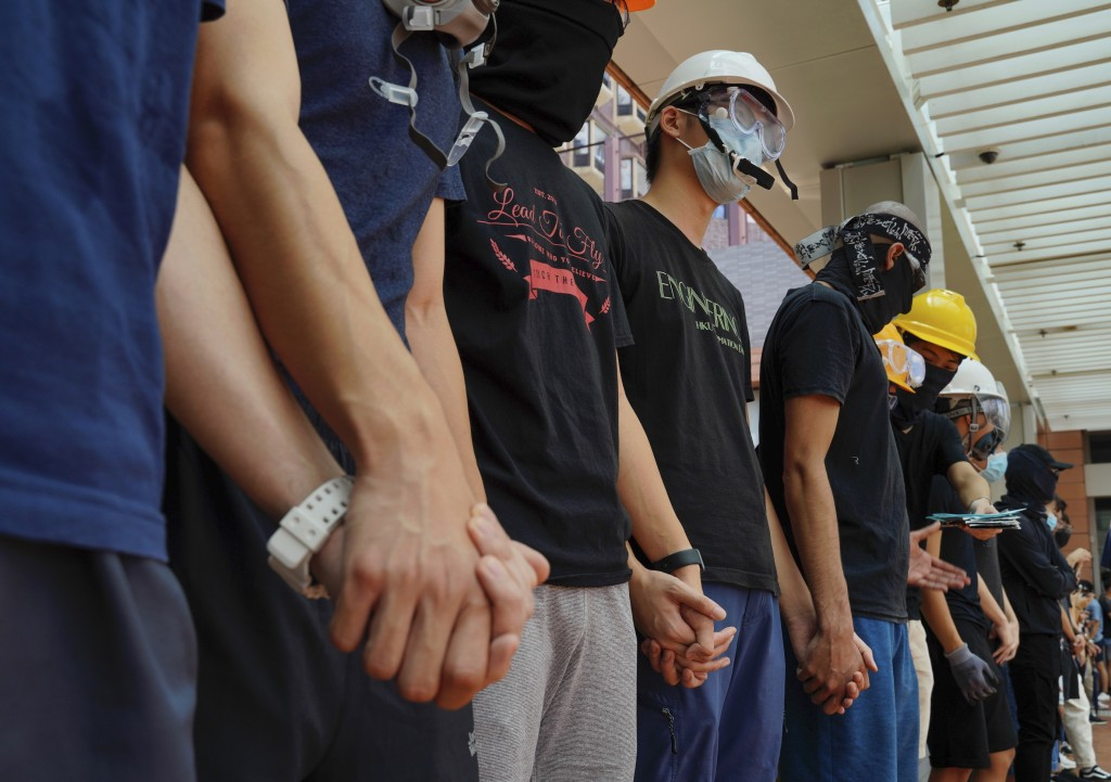 Students from Hong Kong University chains their hands outside schools in Hong Kong, Monday, Sept. 9, 2019. The silent protest comes as the Hong Kong g