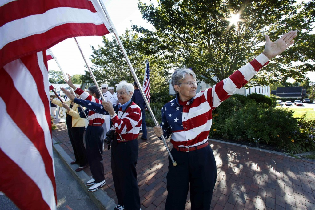 FILE - In this Aug. 23, 2011, file photo, the Freeport Flag Ladies, Carmen Footer, from left, JoAnn Miller and Elaine Greene, wave to vehicles in Free