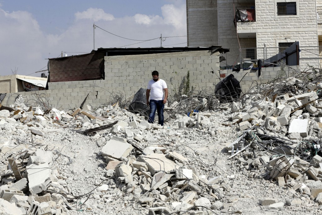 In this Monday, Sept. 9, 2019 photo, Palestinian Jihad Rajabi walks on the rubble of his house that was demolished by Israeli authorities, in the east...