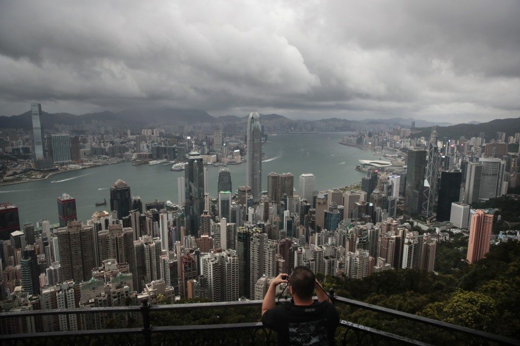 In this Sunday, Sept. 1, 2019 photo, a man sets up his camera in the Victoria Peak area to photograph Hong Kong's skyline. Life is not quite normal af...