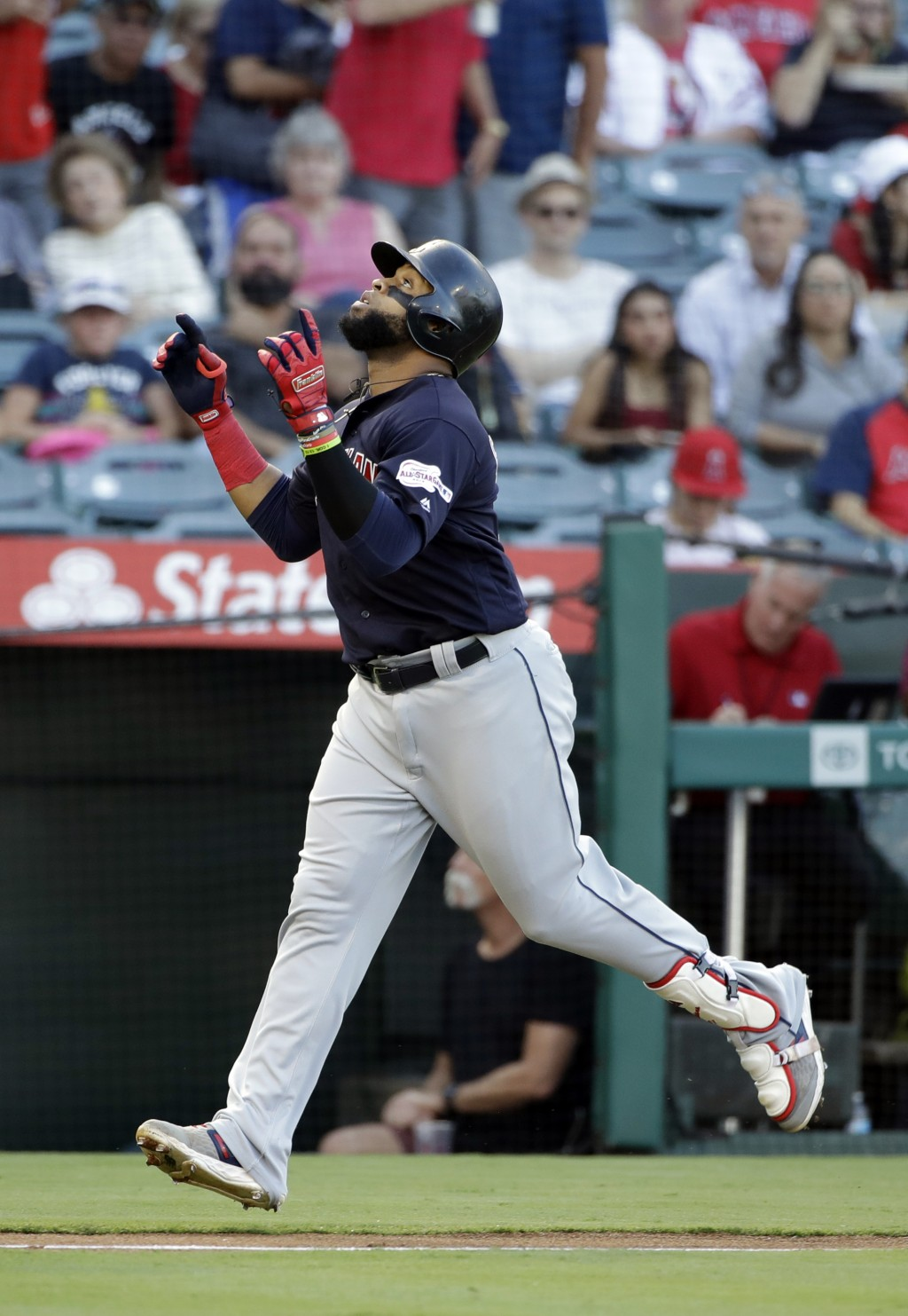 Cleveland Indians' Carlos Santana points skyward as he reaches home plate after his solo home run against the Los Angeles Angels during the first inni...