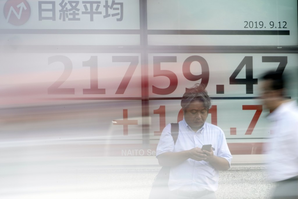 A man stands near an electronic stock board showing Japan's Nikkei 225 index at a securities firm in Tokyo Thursday, Sept. 12, 2019. Asian shares were