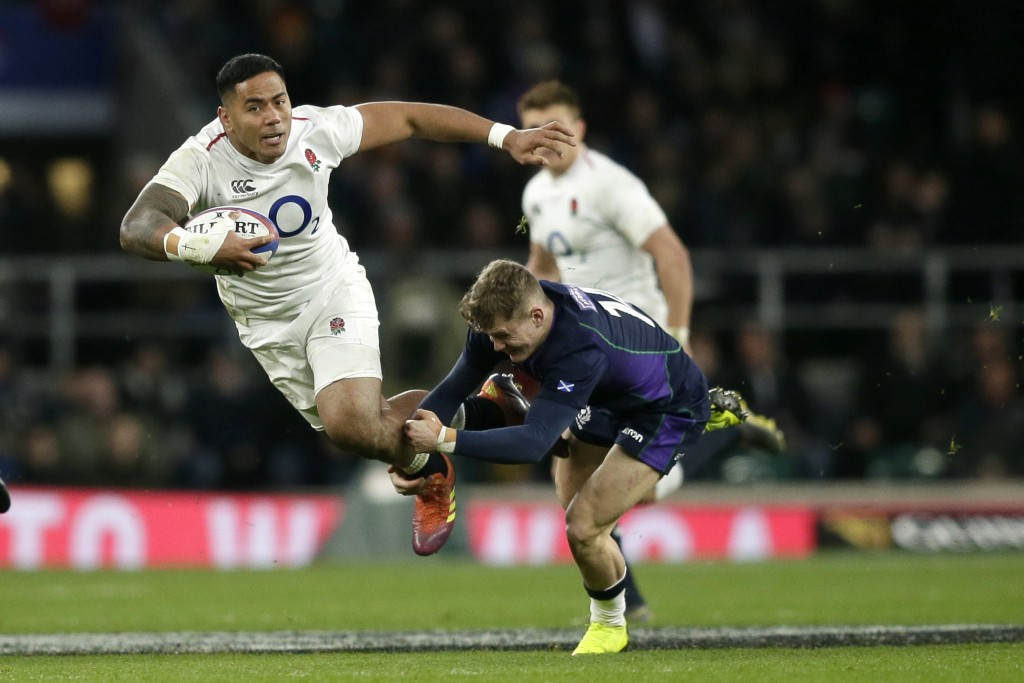 FILE - In this March 16, 2019, file photo, England's Manu Tuilagi, left, is tackled by Scotland's Darcy Graham during the Six Nations rugby union inte