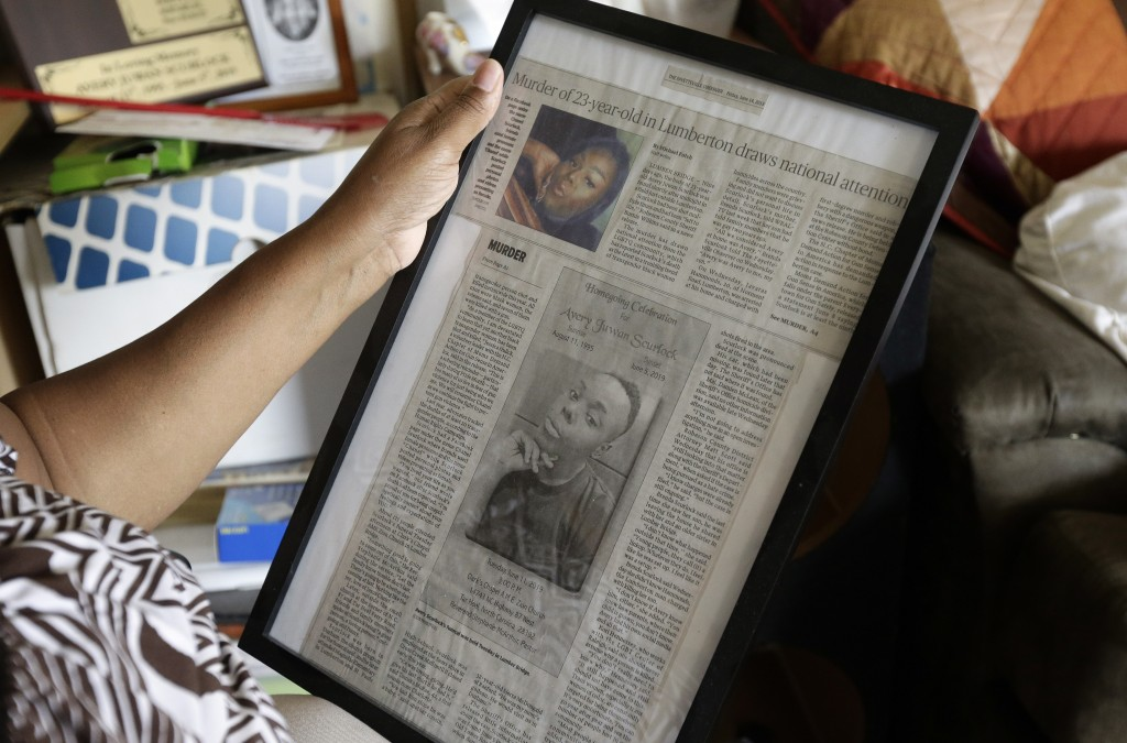 In this photo taken Tuesday, Aug. 6, 2019, Brenda Scurlock is shown in her home in Lumber Bridge, N.C. holding a newspaper clipping about her son's mu