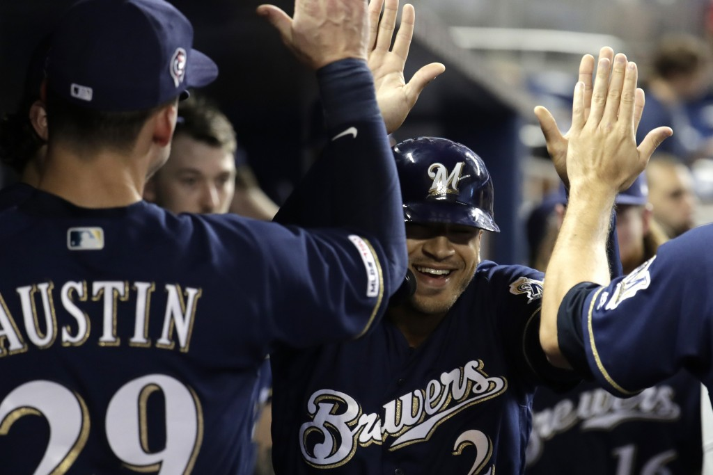 Milwaukee Brewers' Trent Grisham is congratulated after hitting a solo home run during the first inning inning of the team's baseball game against the...