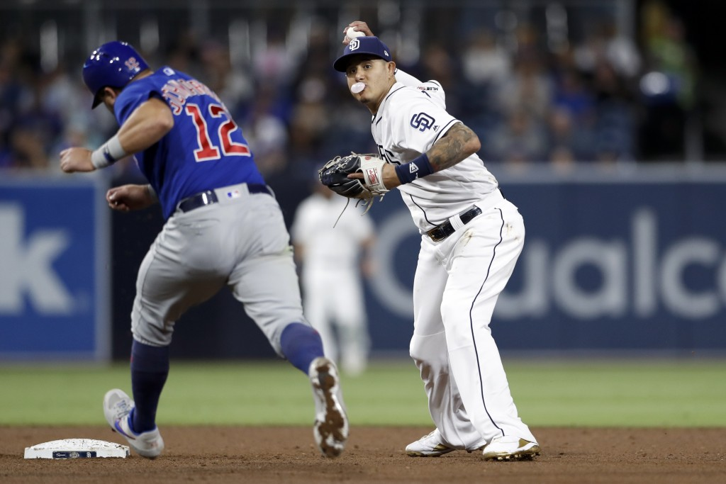 San Diego Padres third baseman Manny Machado, right, throws to first after forcing out Chicago Cubs' Kyle Schwarber, left, at second during the fifth ...