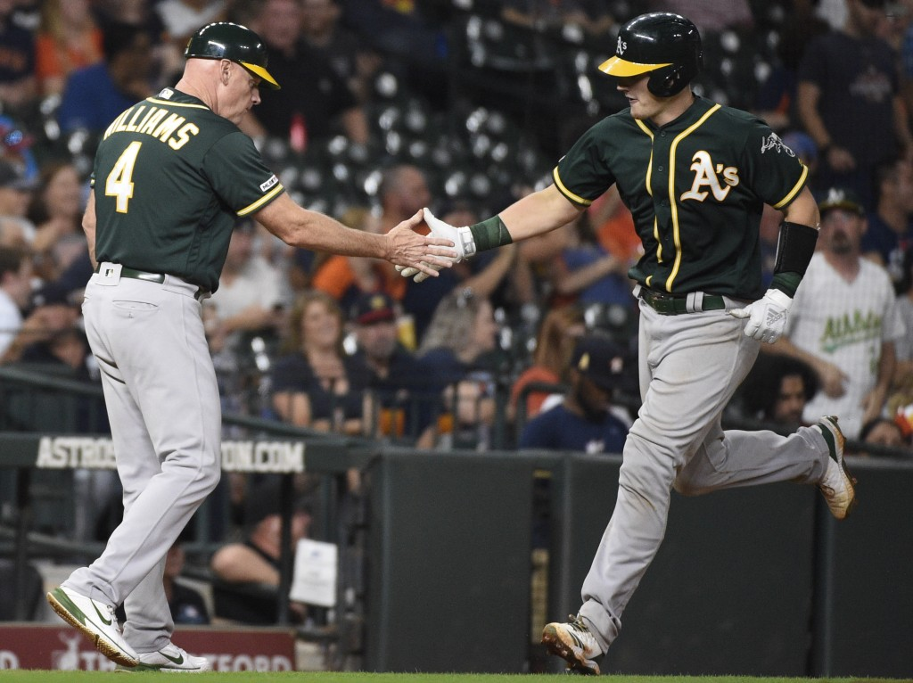 Oakland Athletics' Sean Murphy, right, shakes hands with third base coach Matt Williams after hitting a solo home run off Houston Astros relief pitche...