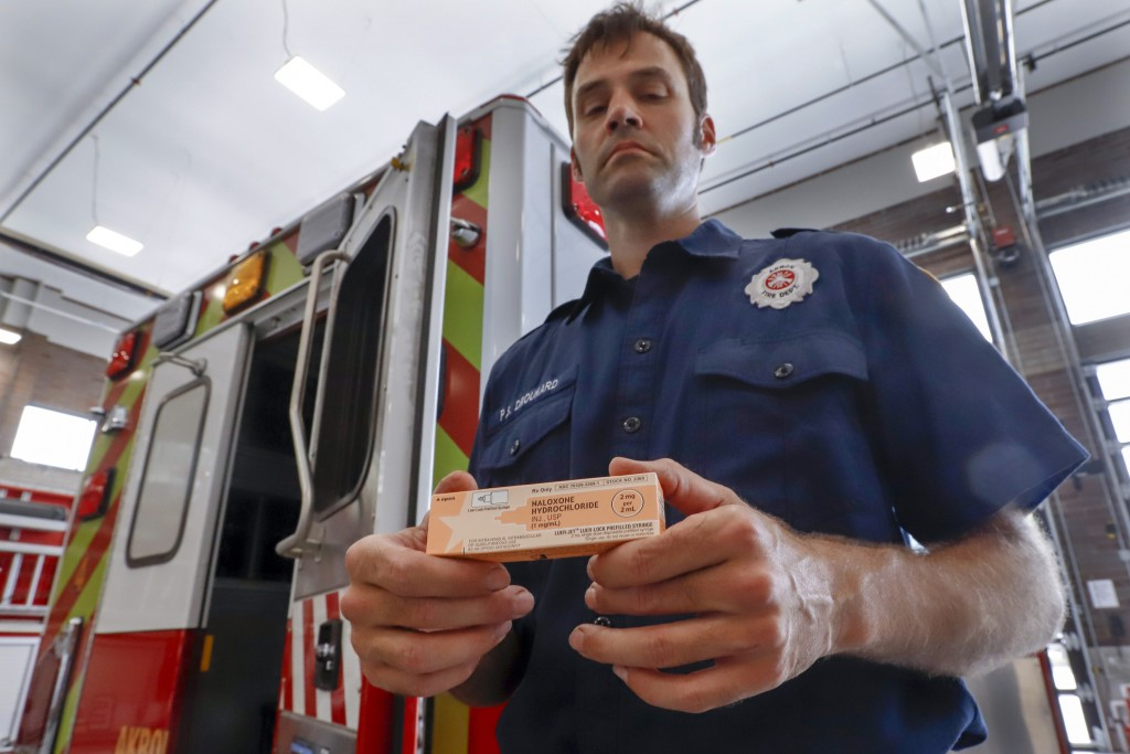 In this Sept. 11, 2019, photo, Akron fire medic Paul Drouhard shows a box containing naloxone that is carried in all the department's emergency vehicl