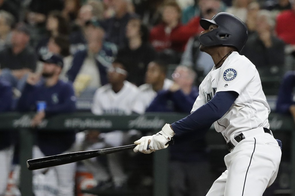 Seattle Mariners' Kyle Lewis watches his three-run home run against the Cincinnati Reds during the seventh inning of a baseball game Wednesday, Sept. ...