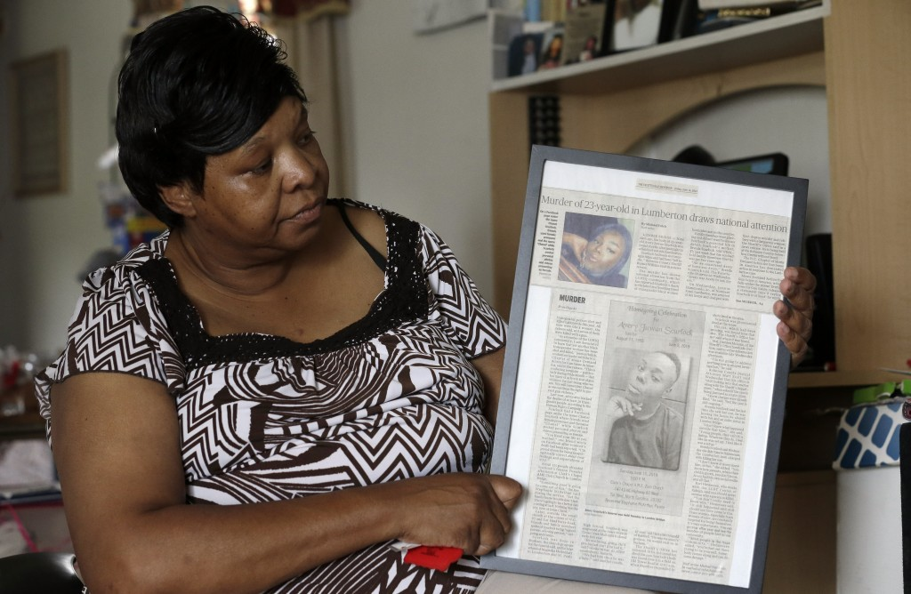 In this photo taken Tuesday, Aug. 6, 2019 Brenda Scurlock is shown in her home in Lumber Bridge, N.C. holding a newspaper clipping about her son's mur...