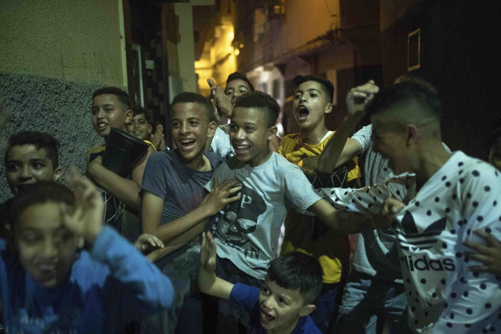 In this Monday, Sept. 9, 2019 photo, youths and children react during the celebration of Ashura, in Sale, near Rabat, Morocco. On Sept. 9, the Arab an...