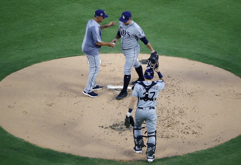 Tampa Bay Rays manager Kevin Cash, top left, takes the ball from starting pitcher Andrew Kittredge, right, as catcher Travis d'Arnaud (37) looks on in