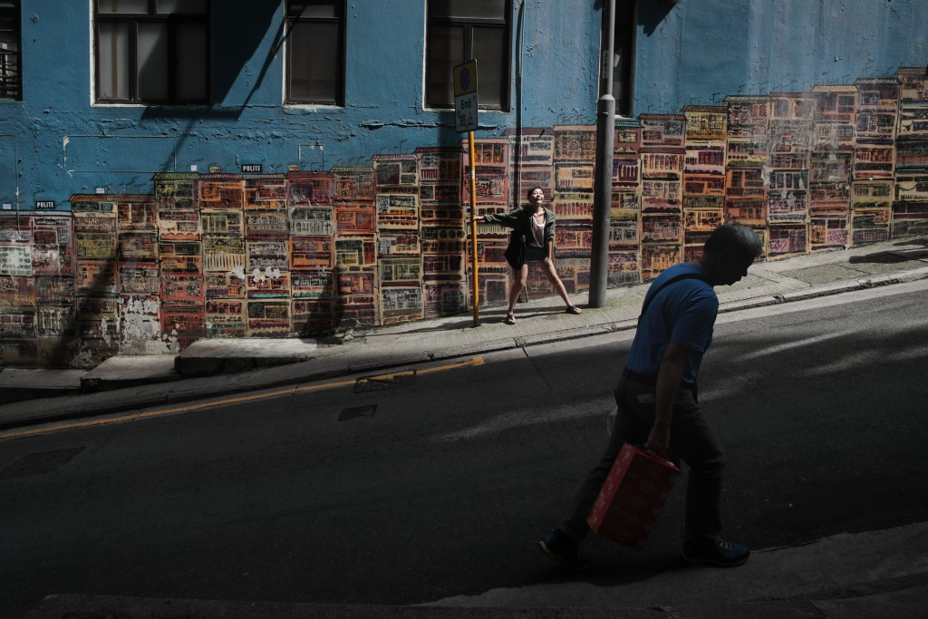 In this Sept. 3, 2019, photo, a tourist poses for photos in front of a popular mural by artist Alex Croft Saturday in the SoHo district of Hong Kong. ...