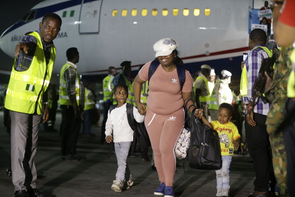 A woman and her children returning from South Africa due to recently violence targeted at foreigners arrive on an Air Peace airline at the Murtala Muh...