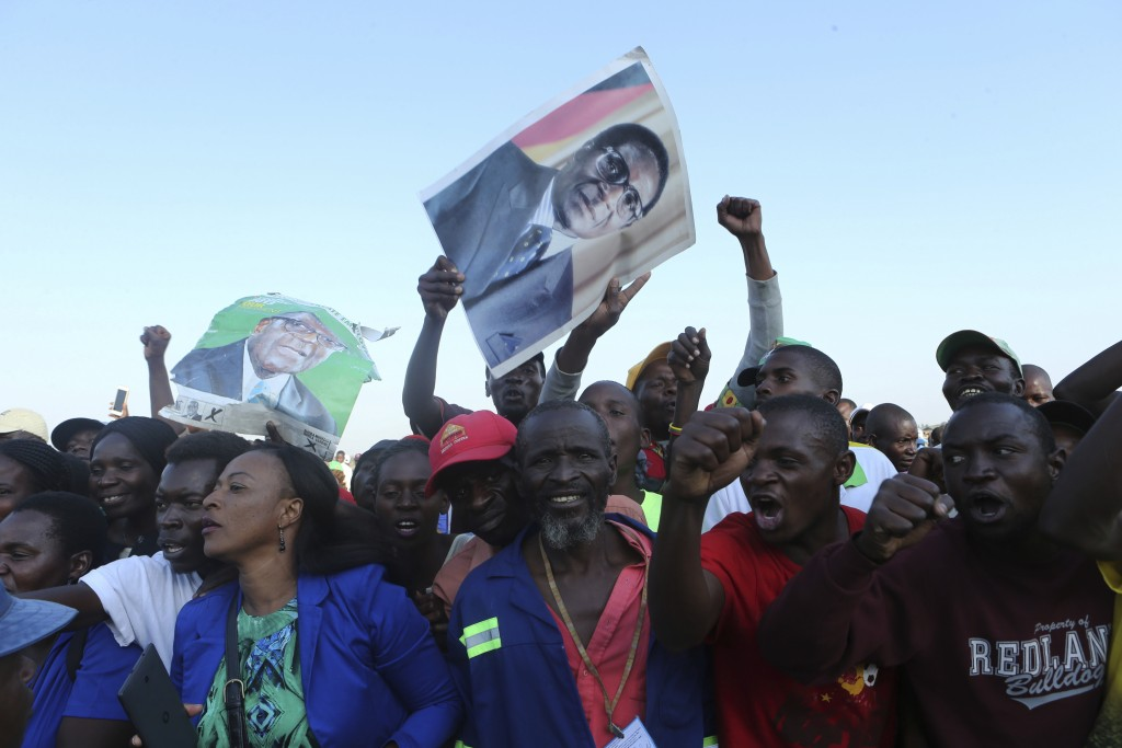 Supporters of Zimbabwe's former ruler, Robert Mugabe react upon the arrival of his remains at at RG Mugabe airport in Harare,Wednesday, Sept, 11, 2019