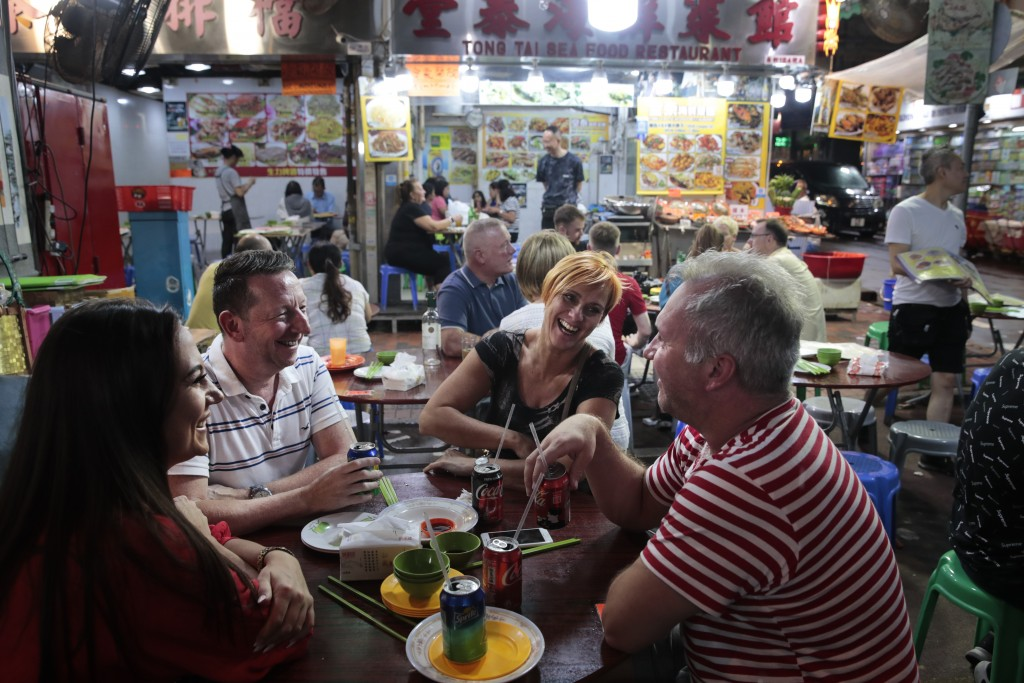 In this Sept. 2, 2019, photo, a group of British tourists share a laugh around a dinner table at Temple Street Night Market in Hong Kong. Life is not ...