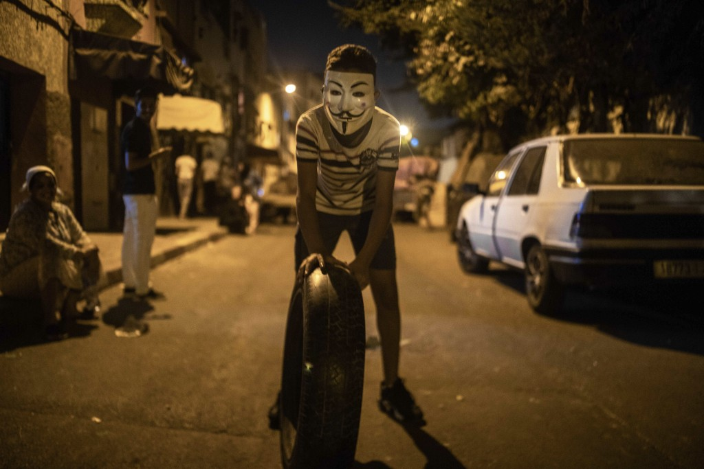 In this Monday, Sept. 9, 2019 photo, a boy wearing a vendetta mask drags a tire to be lit in a bonfire as part of Ashura celebrations, in Sale, near R...
